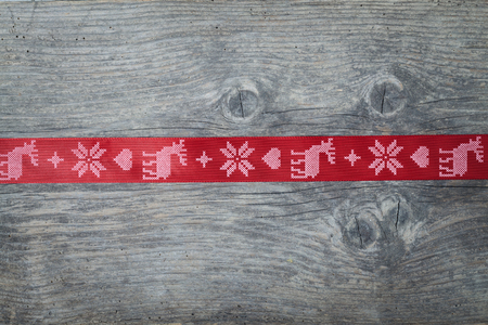 Red christmas ribbon on old wooden backround photo