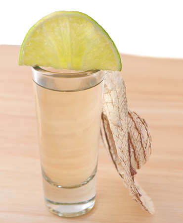 tequila shot with lime and mexican sombrero on wood board and white background