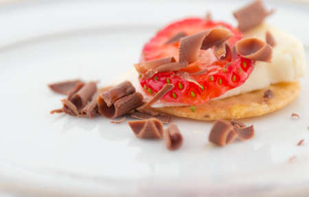 Strawberry and cheese over cracker with chocolate shavings and honey on white plate