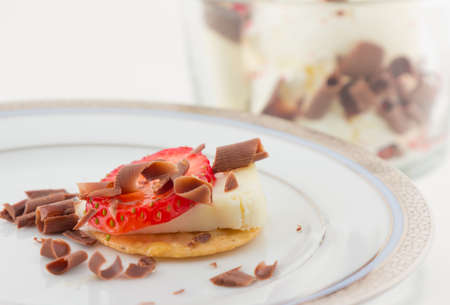 Strawberry, cheese and chocolate shavings on cracker with vanilla ice cream with chocolate shavings on background photo