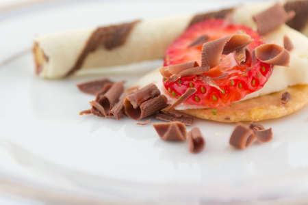 Strawberry and cheese over cracker with chocolate shavings and honey on white plate with wafer