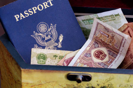 emigration: US passport with chinese currency in a wood box