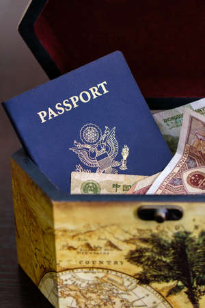 vertical shot of US passport with chinese currency in wood box Stok Fotoğraf