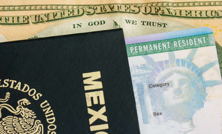 naturalization: Permanent resident card  green card  with a mexican passport over a dollar bill