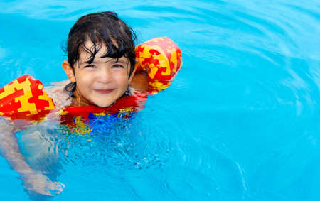 Cute little girl with hazel eyes and enjoy her time in the swimming pool photo
