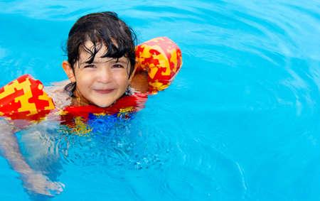Schattig klein meisje met bruine ogen en geniet van haar tijd in het zwembad Stockfoto