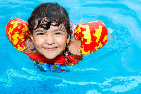 a cute little girl with hazel eyes, wearing an inflatable life vest, having fun in swimming pool