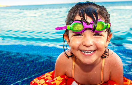 A beautiful happy little girl smiling with pink and green googles and colorful life vest in infinity pool Archivio Fotografico