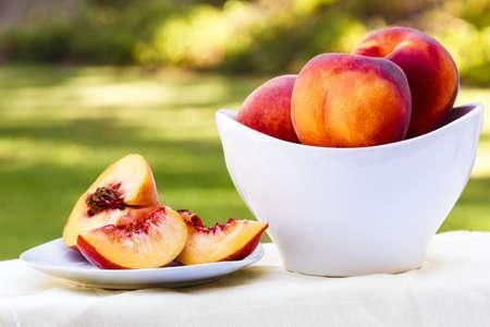 Delicious sliced peach on a garden table with green backdrop