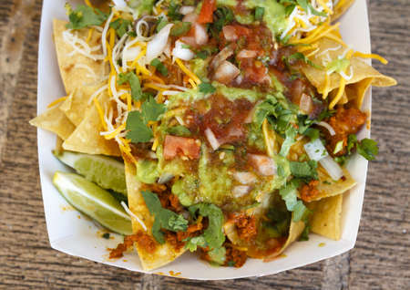 A delicious plate of nachos with meat topped with guacamole and fresh salsa photo