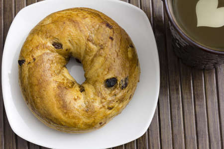 A delicious raisin cinnamon bagel and hot drink with heart shaped milk decoration