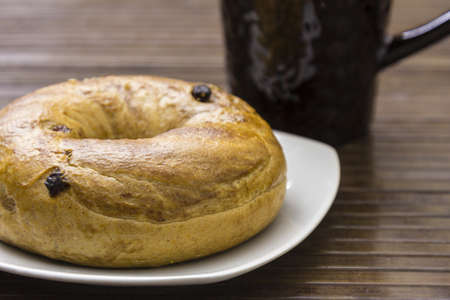 A close-up shot of a delicious raisin cinnamon bagel and a cup of coffee
