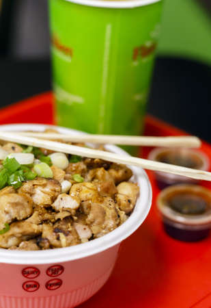 A bowl of chicken with rice, teriyaki style.