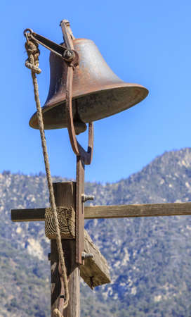 A rusted bell on a wood frame in a farm overlooking the mountains