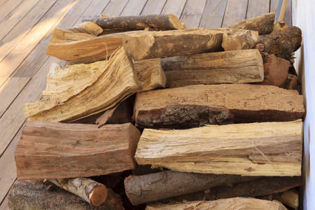 A stack of recenty cut firewood in the backyard patio porch