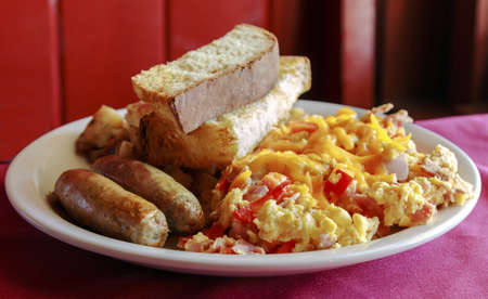 Delicious scrambled eggs with cheese, sausage, potatoes and toast for breakfast