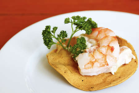 A delicious mexican style appetizer - shrimp on a toasted corn tortilla