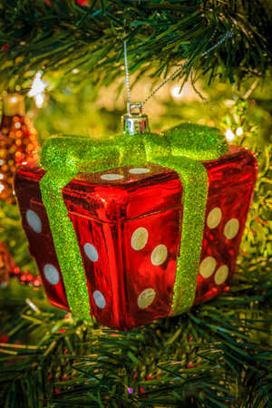 A colorful gift ornament hanging from a Christmas tree
