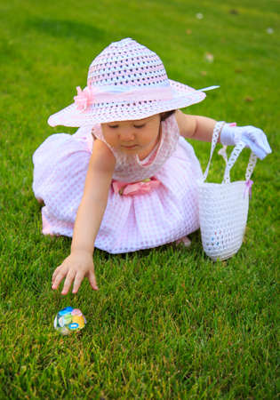 A beautiful little girl in a delightful Easter-themed dressed enjoying the Easter Egg Hunt while holding a basket