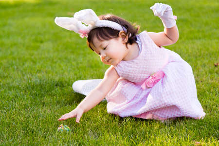 A cute little girl finds an Easter Egg during and Egg Hunt Stok Fotoğraf