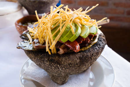 A delicious mexican style carne asada with avocado, meat, chorizo, nopales and tortilla strips served in a stone dish (molcajete) Stok Fotoğraf