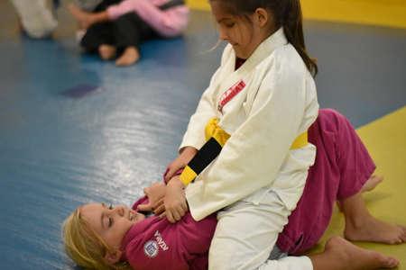 Two kids fighting jiu jitsu on mat using pink and white gi Editorial