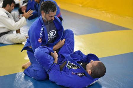 Two friends fight brazilian jiu jitsu on mat with blue gi