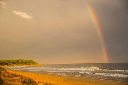 Sunset and rainbow in Platja Llarga beach, Tarragona, Spain