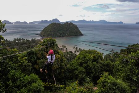 Young adult zip lining between islands