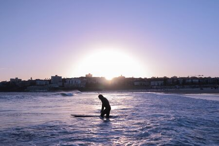 Sunset time at Bondi Beach and surfers trying to catch their last waves