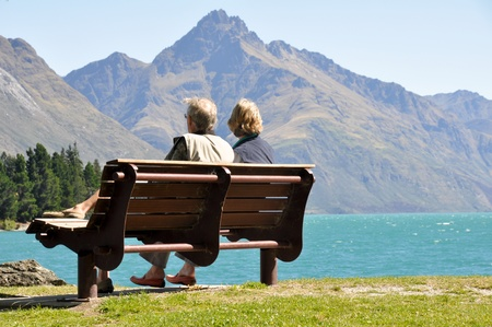 Rear view of a senior couple sitting on a park bench Stock Photo
