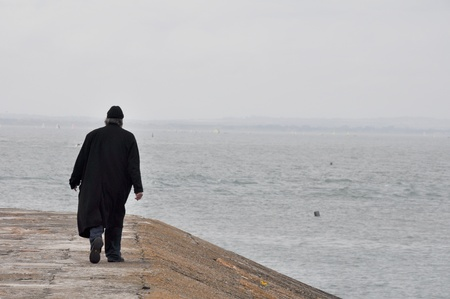 man behind: Lonely man walking at Howth harbour, Ireland