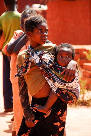zambia: Young woman takes her child in arms on August 10, 2009 in North Lwanga National Park  Zambia