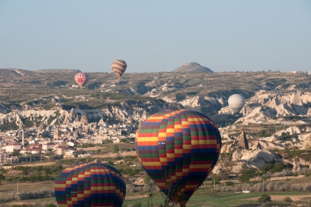 Hot air balloon flies over Cappadocia, the best attraction for tourists, on April 30, 2013 in Cappadocia, Turkey