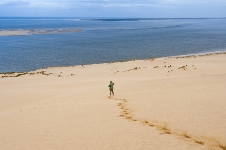 Woman goes down the Great Dune of Pyla, Arcachon, France