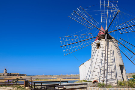 The salt flats with a windmill of Trapani, Sicily, Italy Stock Photo