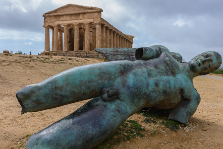 icarus: Icarus statue and Temple of Concordia in the Valley of Temples near Agrigento, Sicily, Italy Stock Photo