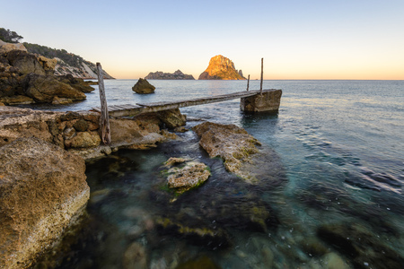 vedra: Small wooden pier in Cala dHort beach, Es Vedra as background, Ibiza island, Spain Stock Photo