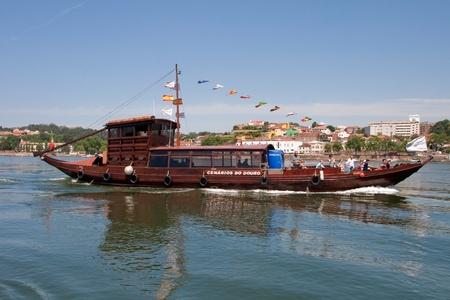 rabelo: Porto, Portugal - May 14, 2011: Changed Rabelo ship carrying tourists between the bridges of the river Douro showing the riverside area of Porto and Vila Nova de Gaia.