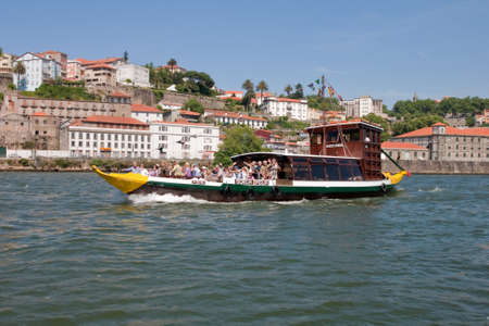 Porto, Portugal - May 14, 2011: Changed Rabelo ship carrying tourists between the bridges of the river Douro showing the riverside area of ​​Porto and Vila Nova de Gaia. Stock Photo - 12298931