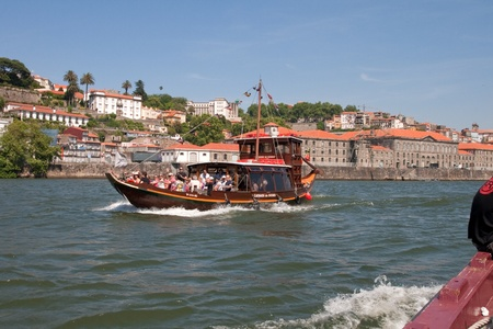 rabelo: Porto, Portugal - May 14, 2011: Changed Rabelo ship carrying tourists between the bridges of the river Douro showing the riverside area of Porto and Vila Nova de Gaia. Editorial