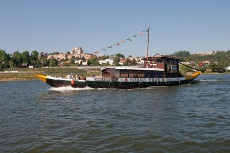 rabelo: Porto, Portugal - May 14, 2011: Changed Rabelo ship carrying tourists between the bridges of the river Douro showing the riverside area of ​​Porto and Vila Nova de Gaia. Editorial