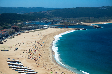 The beach of Nazare is completely integrated in the urban area. It is bordered on the north by the promontory and to the south by the moor of the shelter harbor, conserving in the summer the traditional cloth stalls with stripes of strong colors. Bathed b
