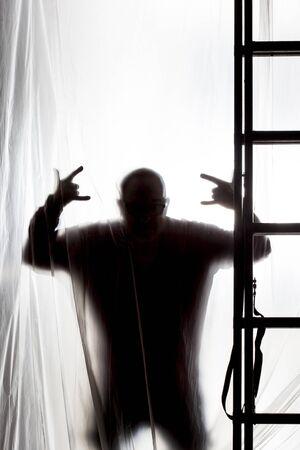 silhouette of man behind a plastic Standard-Bild