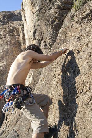 equipped climber climbing a rock