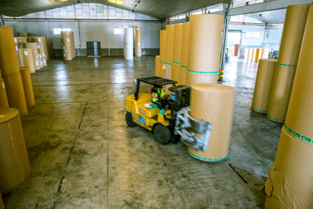 machine transporting a roll of paper in a factory