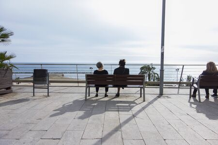 women sitting on a bench in front of the beach in Alicante