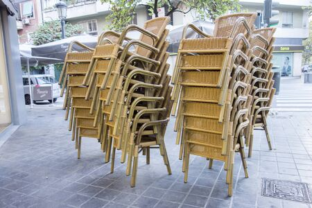 stacked wicker chairs on the street Imagens