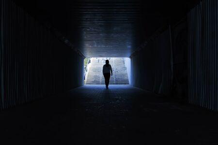 woman crossing a tunnel without light Foto de archivo