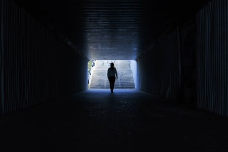 woman crossing a tunnel without light Banco de Imagens
